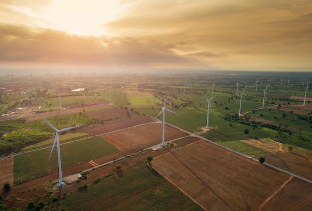 Luchtmening van grote windturbines bij zonsopgang die uit de lucht wordt genomen.