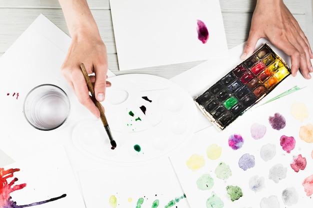 Luchtmening van hand die waterverf voor het schilderen mengen