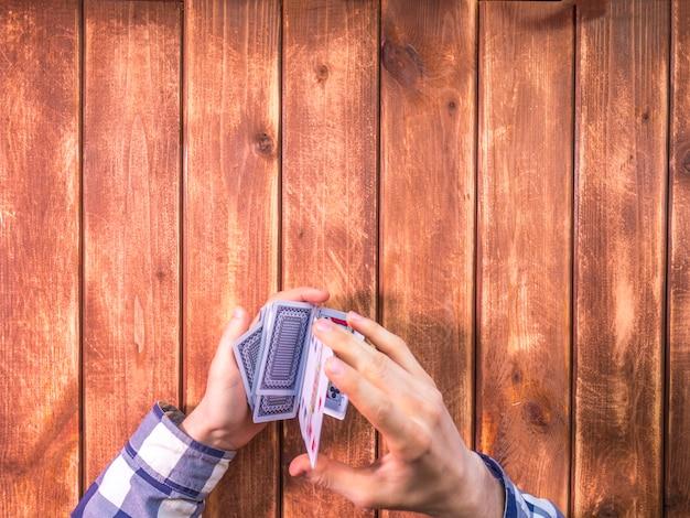 Luchtmening van handen die speelkaarten op de houten oppervlakte mengen