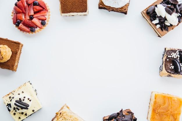 Luchtmening van heerlijke gebakjes die kader op witte achtergrond vormen