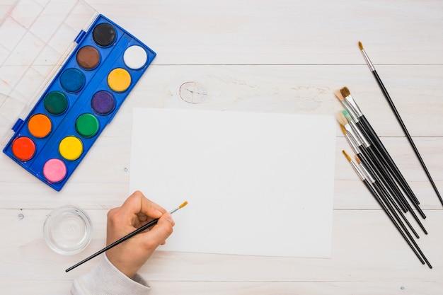 Luchtmening van het menselijke hand schilderen op wit leeg document met verfborstel