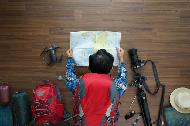 Luchtmening van het plan van de reizigersmens en rugzak met kaart