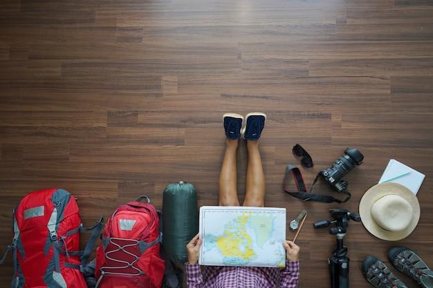 Luchtmening van het plan van de reizigersvrouw en rugzak planning