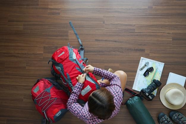 Luchtmening van het plan van de reizigersvrouw en rugzak plannings vakantiereis met kaart