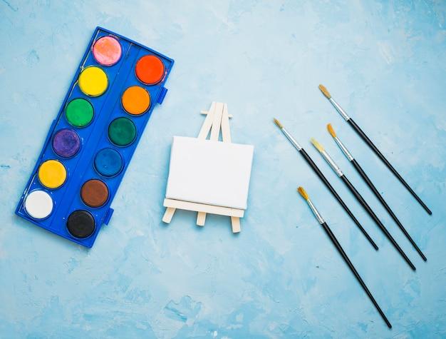 Luchtmening van het schilderen van materiaal op blauwe achtergrond