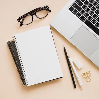 Luchtmening van kantoorbenodigdheden en laptop op beige achtergrond