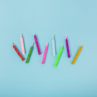 Luchtmening van kleurrijke glanzende kaarsen op blauwe achtergrond