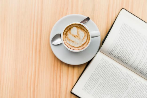 Luchtmening van koffie latte en open boek op houten lijst
