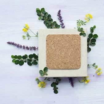 Luchtmening van leeg cork kader met lavendelbloemen en takje op houten achtergrond