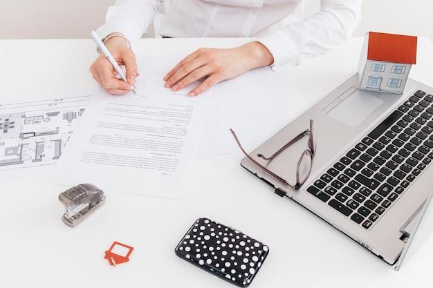 Luchtmening van menselijke hand die handtekening zetten bij officieel document op kantoor