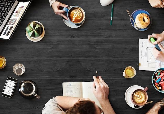 Luchtmening van mensen die bij koffie brainstormen
