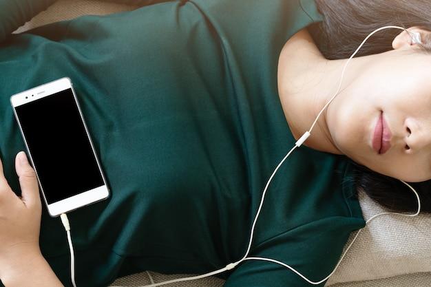 Luchtmening van mooie jonge vrouw die op bank bepalen die smartphone gebruiken om de muziek te luisteren