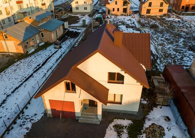 Luchtmening van nieuw woonhuisplattelandshuisje en garage in bijlage met dakspaandak op omheinde werf op zonnige de winterdag op modern gebied in de voorsteden. perfecte investering in droomhuis.