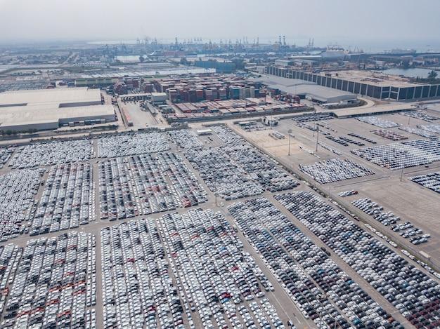 Luchtmening van nieuwe die auto's bij het parkeerterrein van automobiele fabriek worden geparkeerd. wachten op export en import in de internationale haven.