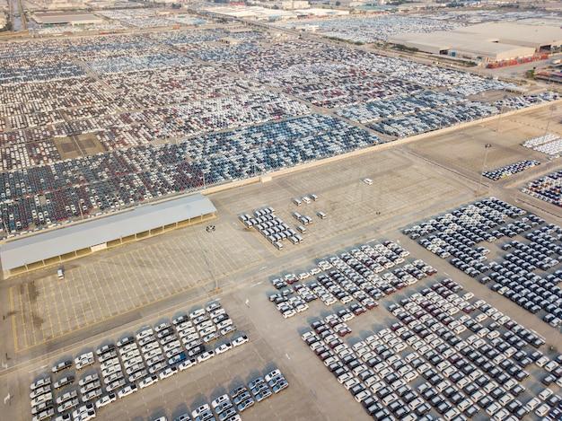 Luchtmening van nieuwe die auto's bij het parkeerterrein van automobiele fabriek worden geparkeerd