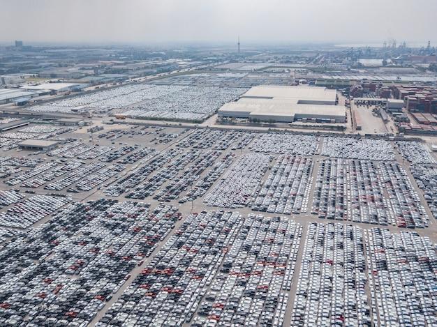 Luchtmening van nieuwe die auto's bij het parkeerterrein van automobiele fabriek worden geparkeerd.