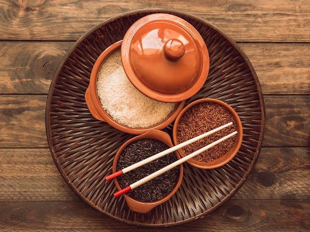 Luchtmening van ongekookte organische rijstkorrelskommen op houten dienblad met eetstokje