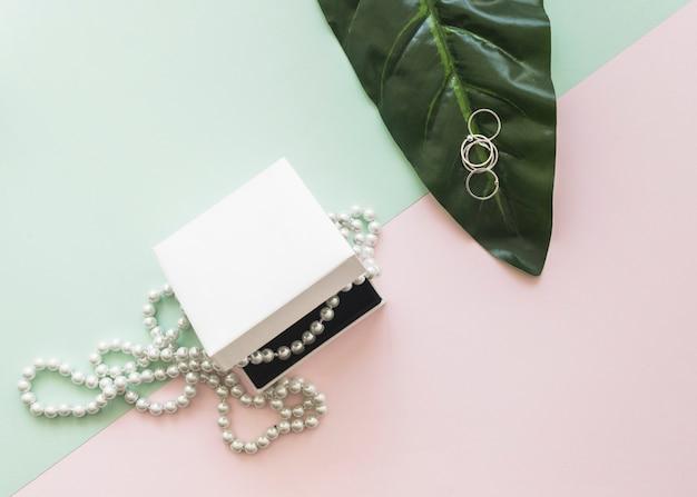 Luchtmening van parelhalsband in witte doos en ringen op blad over de pastelkleurachtergrond
