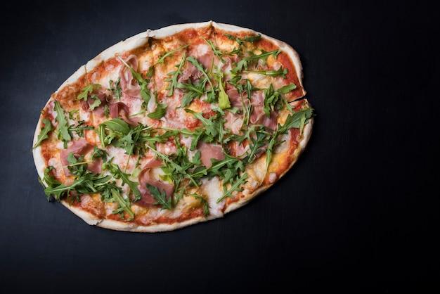 Luchtmening van pizza met bacon en arugula op zwart keukenteller