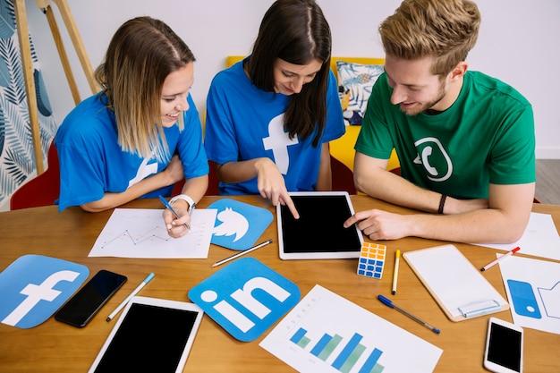 Luchtmening van sociaal media voorzien van een netwerkteam die digitale tablet bekijken