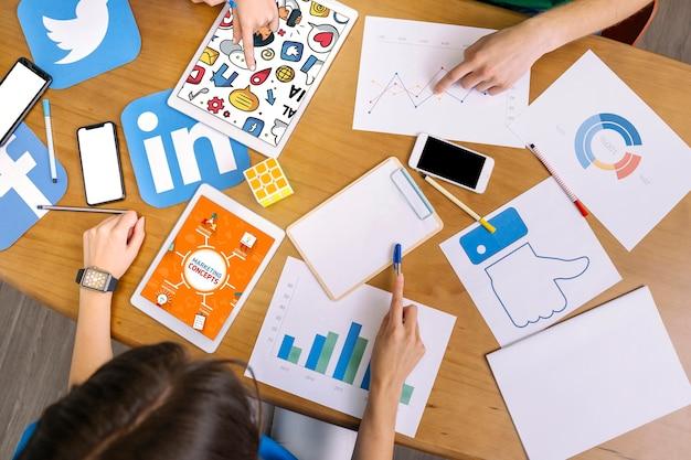 Luchtmening van team die sociale media grafiek analyseren op het werk