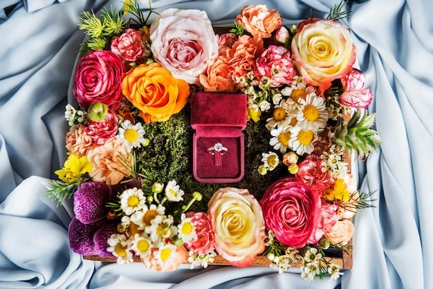 Luchtmening van trouwring in rode doos met de decoratie van het bloemenarrangement