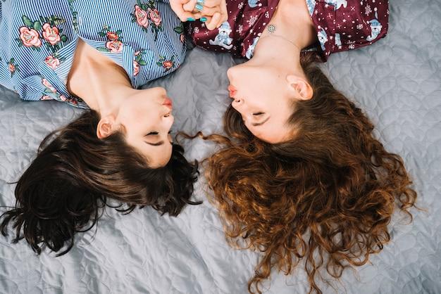Luchtmening van twee vrouwelijke vrienden die lippen pruilen terwijl het liggen op bed