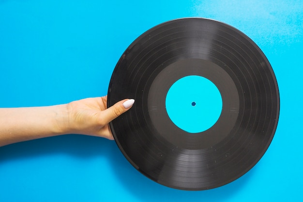 Luchtmening van vrouwelijke handen die vinylverslag op blauwe achtergrond houden