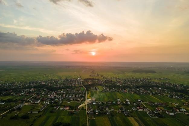 Luchtmening van woonhuizen in landelijk gebied in de voorsteden bij zonsondergang.