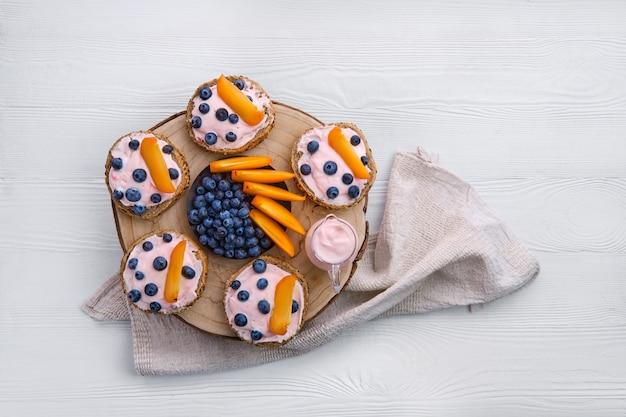 Luchtmening van zoete broodjes met yoghurt, bosbes en plak van dadelpruim op witte houten lijst