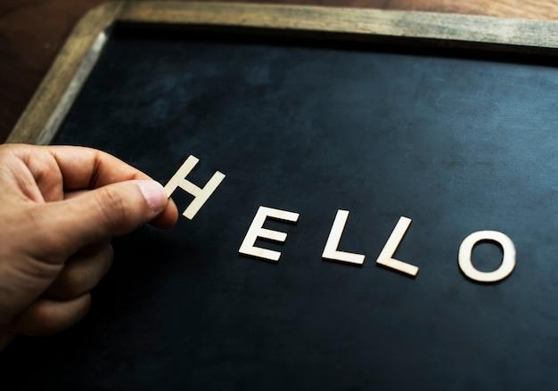 Luchtmening van zwarte raad met de brief die hello groetconcept vormen