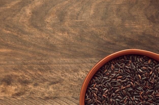 Luchtmening van zwarte rijstkom op rustieke houten lijst