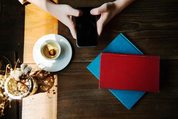 Luchtmeningsclose-up van handen met mobiele telefoon in koffiekoffie op houten lijst
