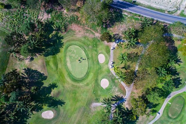 Luchtmeningsfotografie van bos en golfcursus met meer. golf en sportclub.
