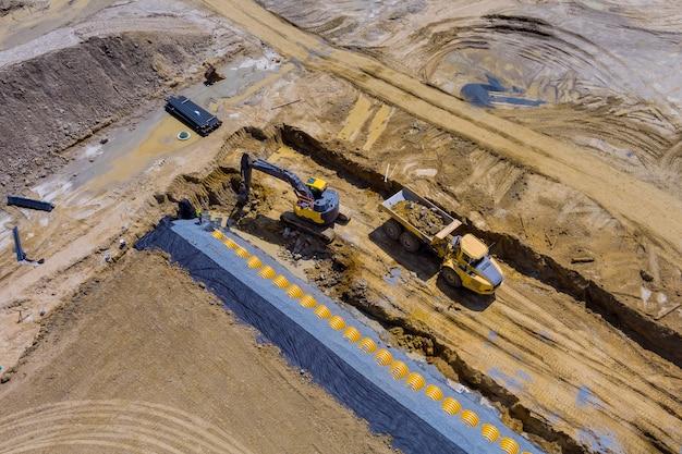 Luchtpanorama op de bouwplaats van zwaar materieel voor de bouw van rioleringen voor het leggen van een extern rioleringssysteem