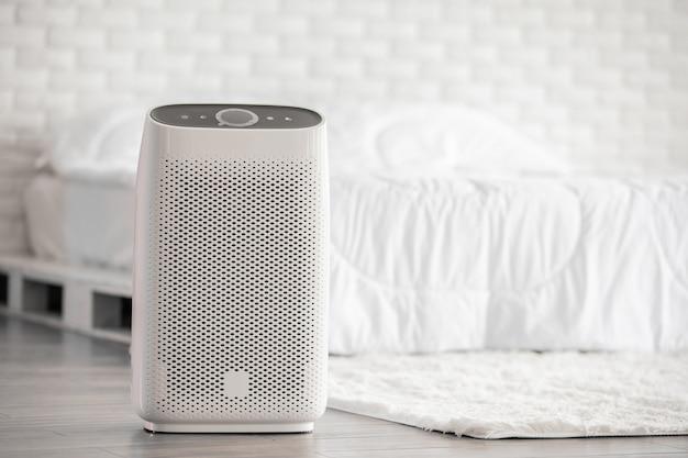 Luchtreiniger in knusse witte slaapkamer voor filteren en reinigen van stof pm2.5 hepa in huis