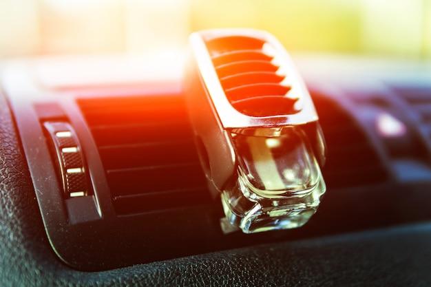 Luchtverfrisser in de auto, zwart interieur, autodeflectors, zonlicht schijnt door de voorruit