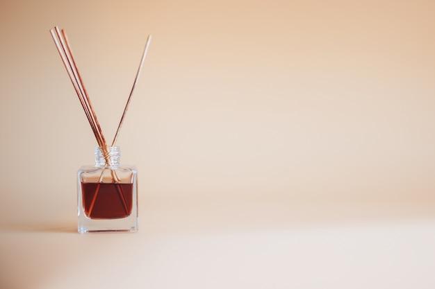 Luchtverfrisser sticks op begie achtergrond glazen pot aroma bamboestokken