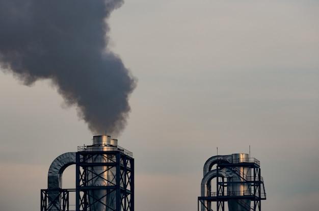 Luchtverontreiniging door fabriek. zwarte rook uit schoorsteen van industriële pijp. opwarming van de aarde probleem concept. emissiefactoren voor luchtverontreinigende stoffen. luchtverontreiniging. pm 2,5 stof. triggers van astma en copd.