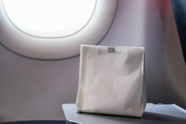 Luchtziek misselijk persoon in de luchtziekte braakselzak bereid om te braken