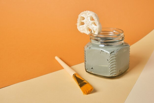 Luffa, penseel, cosmetische klei in een glazen pot op een houten standaard, beige en bruine achtergrond, kopie ruimte