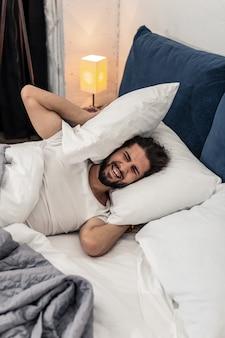 Luide wekker. ongelukkige emotionele man die oren bedekt met kussens terwijl hij wil blijven slapen