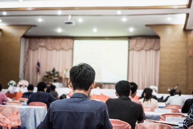 Luidspreker op het podium, achteraanzicht publiek luistert naar spraakdocent in conferentiezaal of seminar vergadering