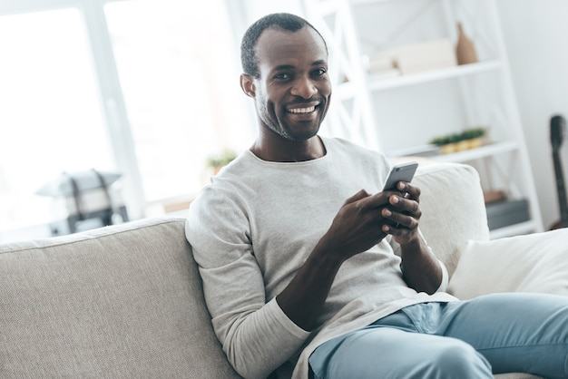 Luie dag thuis. knappe jonge afrikaanse man die een bericht typt en naar de camera kijkt terwijl hij op de bank zit