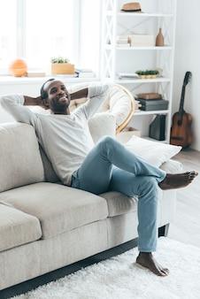 Luie dag thuis. knappe jonge afrikaanse man die handen achter het hoofd vasthoudt en glimlacht terwijl hij thuis op de bank zit