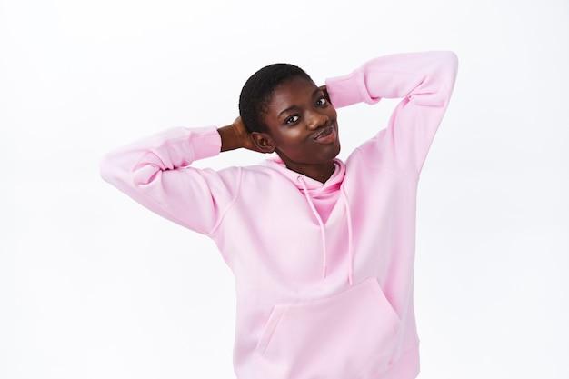 Luie en zorgeloze knappe afro-amerikaanse vrouw in roze hoodie, handen achter het hoofd vasthouden, kantelen en vrolijk glimlachen