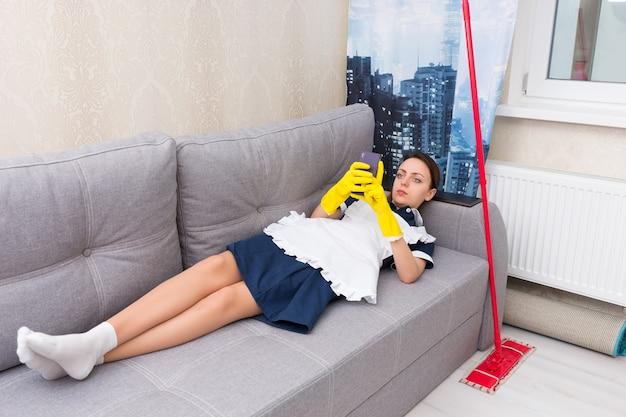 Luie indolente meid of huishoudster in uniform liggend ontspannen op een comfortabele bank met haar dweil naast het controleren van haar mobiele telefoon
