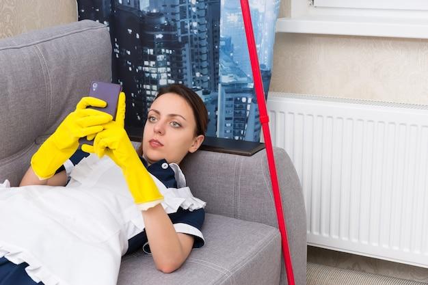Luie jonge huishoudster of meid in een net uniform en schort ontspannen op een bank die een pauze neemt om haar sms-berichten op haar mobiel te lezen