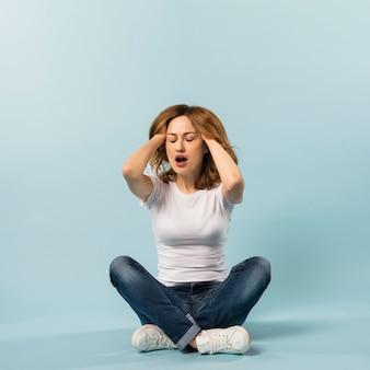 Luie jonge vrouw met haar twee handen in het haar tegen blauwe achtergrond