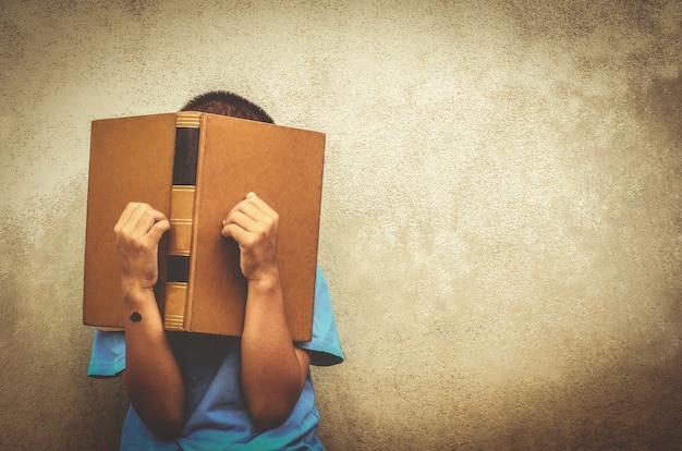 Luie jongen leest het boek onderwijs concept asia jongen geboorteaanduiding op linkerpols
